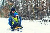 Happy Mother And Her Son Enjoying Sleigh Ride. Happy Family With Sled In Winter Having Fun Together. poster