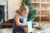 Happy Child Girl Opens Gift Box Under Christmas Tree. Kid Is Surprised. Natural Children Emotions. C poster
