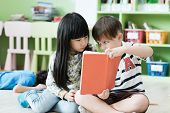 American Boy And Asian Girl Are Reading Together With Happiness In Their Kindergarten Classroom, Kid poster