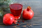 Ripe Pomegranate Fruit And A Glass Of Pomegranate Juice On Wooden Table. Healthy Eating Concept. poster