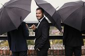 Stylish Groom And Groomsmen Standing Under Black Umbrella And Posing. Confident Man In Suit Holding poster