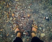 A Feet With Brown Sandals On Different Colored Stones Can Be Use As Background For Sandals Advertise poster