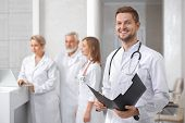 Medical Staff Of Professional, Private Hospital. Handsome Male Doctor Standing, Looking At Camera An poster