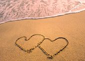 stock photo of beach sunset  - two hearts drawn in beach in sunset - JPG