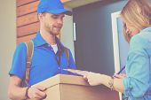Smiling Delivery Man In Blue Uniform Delivering Parcel Box To Recipient - Courier Service Concept. S poster