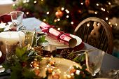 Christmas table setting with a Christmas cracker arranged on a plate with red and green table decora poster