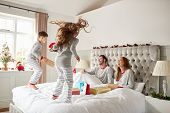 Excited Children Jumping On Parents Bed At Home As Family Open Gifts On Christmas Day poster