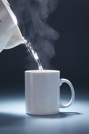 stock photo of hot water  - stock image of pouring hot drink to the mug - JPG