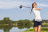 Girl golf player teeing off with driver from tee box, front view.