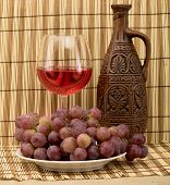 foto of loamy  - Stil life with carafe grape and goblet on mat - JPG
