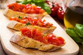 stock photo of oregano  - fresh bruschetta on a wooden cutting board - JPG