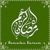 Arabic Islamic calligraphy of text Ramadan Kareem on floral decorated green background.
