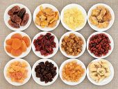 stock photo of pawpaw  - Dried fruit assortment in white porcelain bowls over hessian background - JPG