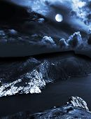 stock photo of moonlit  - moonlit night and clouds on night sky in the sea - JPG