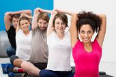 foto of stretching exercises  - Diverse multiethnic group of fit young friends exercising together in class at the gym sitting cross legged on their mats doing stretching exercises - JPG