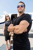 stock photo of bodyguard  - Bodyguard with arms crossed standing against woman and private jet - JPG