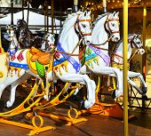 foto of carousel horse  - Traditional carousel with running horses for the children - JPG