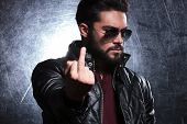stock photo of obscene gesture  - fashion man in leather jacket and sunglasses flipping you off - JPG