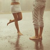A loving young couple hugging and kissing under a rain. Two lovers, man and woman barefoot in the sh