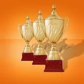 stock photo of plinth  - Receding row of gold trophy cups with lids on wooden plinths with orange background - JPG