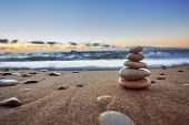 stock photo of peace  - Stones balance on beach sunrise shot - JPG