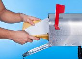 stock photo of mailbox  - Man opening his mailbox to remove mail inside close up of his hand on the open door against a blue sky - JPG