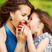 stock photo of early spring  - Mother and her child enjoy the early spring eating apple happy - JPG