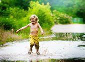picture of wet feet  - Little boy runs through a puddle - JPG