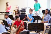 foto of orchestra  - Pupils Playing Musical Instruments In School Orchestra - JPG