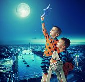 stock photo of reach the stars  - Young brothers reaching stars - JPG