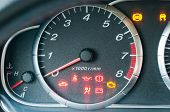 stock photo of illuminating  - Closeup of car tachometer with many illuminated indicators - JPG