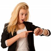 stock photo of running-late  - Young blonde woman looks at her watch when she is being late isolated over white background - JPG