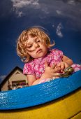 pic of creeping  - Little girl looking at the snail creeping on top of the sandpit - JPG