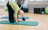image of physical therapist  - Senior woman bending forward and touching her toes being helped by gym instructor - JPG