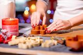 foto of christmas cookie  - Making ginger cookie on Christmas decorated table on festive lighting background - JPG