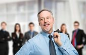 stock photo of leader  - Portrait of a mature leader in front of his team of business people - JPG