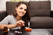 picture of home remedy  - Pretty young Hispanic brunette using a pill organizer to sort her vitamins out at home - JPG