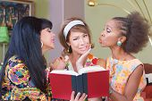 stock photo of tawdry  - Three diverse sentimental mature women reading book - JPG