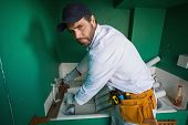 stock photo of frown  - Construction worker frowning at camera in a new house - JPG