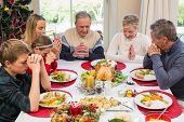 picture of extended family  - Extended family saying grace before christmas dinner at home in the dining room - JPG