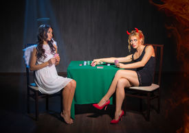 stock photo of sharpie  - Angel and devil playing cards at room - JPG