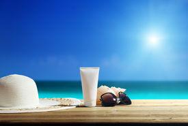 stock photo of sun tan lotion  - Sun lotion and sunglasses on the beach - JPG