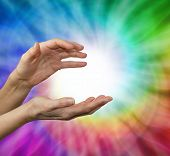 foto of senses  - Female hands cupped in energy sensing position with a rainbow vortex behind and a ball of white energy in the center - JPG