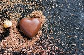 image of chocolate-chip  - Chocolate heart in chocolate chips on a black background - JPG