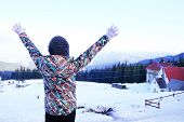 picture of turn-up  - Woman in warm clothing turned back raising her hands up over Carpathian Mountains in wintertime - JPG