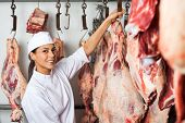 picture of slaughterhouse  - Portrait of mid adult female butcher hanging meat in butchery - JPG