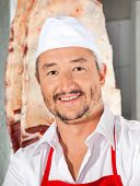 stock photo of slaughterhouse  - Portrait of confident mature male butcher smiling in butchery - JPG