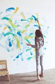picture of wall painting  - 8 years old girl painting the wall at home - JPG