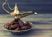image of aladdin  - Dates and golden arabian lamp on wooden background - JPG