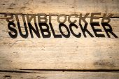 stock photo of heatwave  - wooden letters on old aged wooden table build the shadow word sunblocker vintage style - JPG